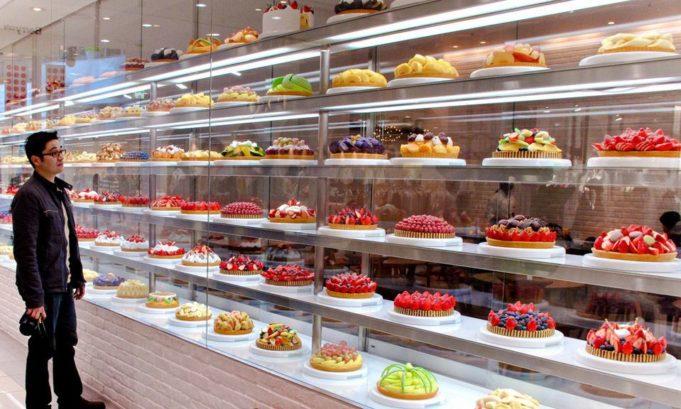 Un jeune homme japonais entrain de choisir un gâteau français au supermarché